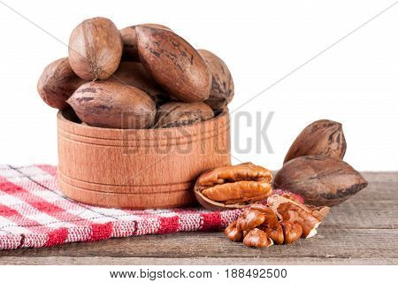 pecan nuts in a wooden bowl on the old board with white background.