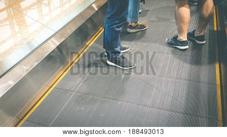 Asia group tourist use long horizontal escalator at international airport terminal. Legs of tourist standing on horizontal escalator with copy space for background.