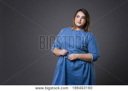Plus size fashion model in casual clothes fat woman on gray studio background overweight female body