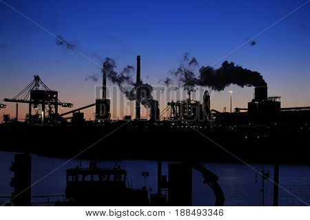 Skyline of an industrial area during sunset poster