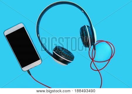 Headphones isolated on cyan background Concept listen to music from smartphone