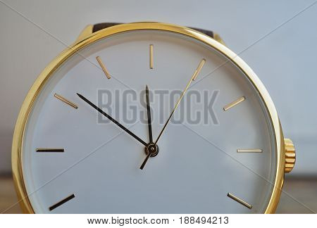 Macro detail of a luxurious golden wrist watch with a white dial on the wooden background as a symbol of and expensive timepiece