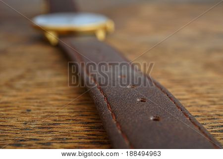 Macro detail of a brown leather wrist watch strap on the wooden background