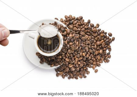 pouring sugar with teaspoon on cup of coffee on white background