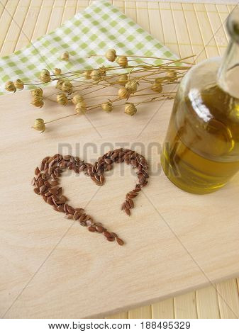 Heart made of linseed and bottle of flaxseed oil