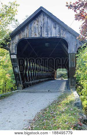 Narrow covered bridge across Contoocook River in Henniker New Hampshire