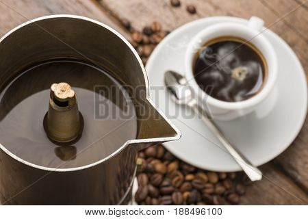 coffeepot closeup and cup of coffee on wooden table