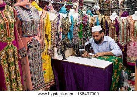 Muscat Oman - March 15 2017: Friendly local tailor working at a traditional sewing machinemaking women dresses in Muscat Oman