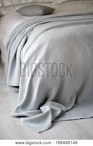 Neutral coloured textured bedspread / throw on a bed