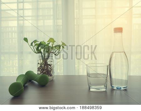 wood office table with glasses and bottle of water green weight dumbbell glass flowerpot of plant on blurry beautiful white drape window texture background.