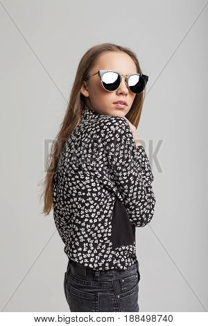 Portrait of young beautiful girl with black sunglasses over gray background. woman dressed in black T-shirt, black jeans and white shoes