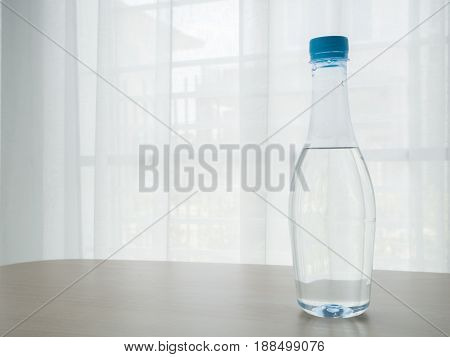 wood table with bottle of pure water on blurry beautiful white drape window texture background.