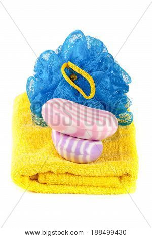 Yellow towel with blue bath sponge and soap isolated on white background.