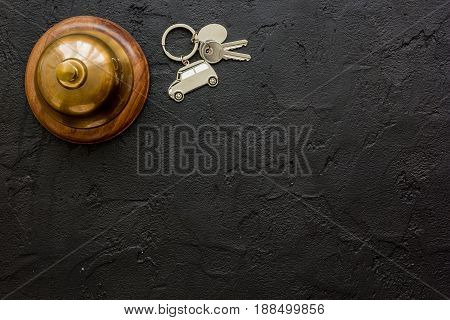 booking hotel room, ring and keys on dark stone desk background top view mock up
