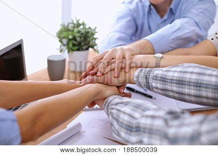 Business people joining hands over table. Start up team