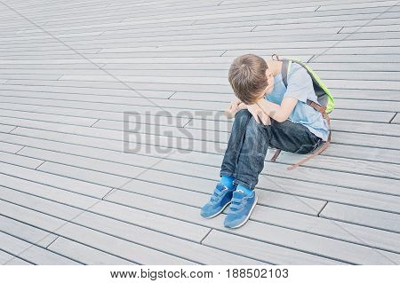 Sad, lonely, unhappy, tired, disappointed child sitting alone on the ground outdoors