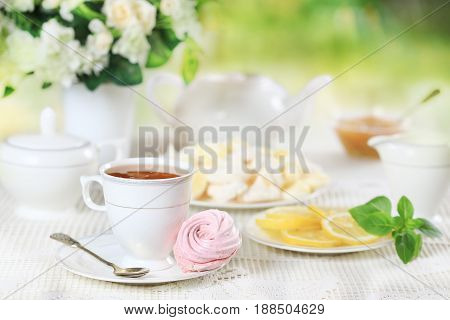 Cup of hot tea with pink marshmallow and lemon on white table with a bouquet of flowers
