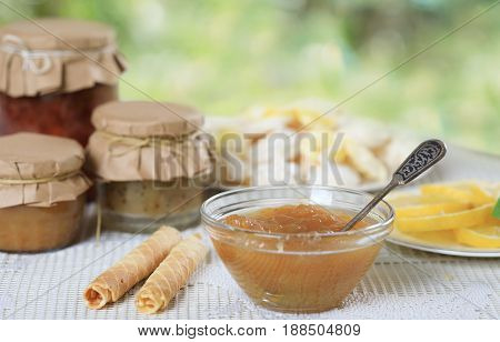 Various homemade jam with waffle and lemon on a white table
