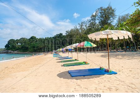 Sand Beach With Line Of Empty Sunbeds And Parasol Sunshade