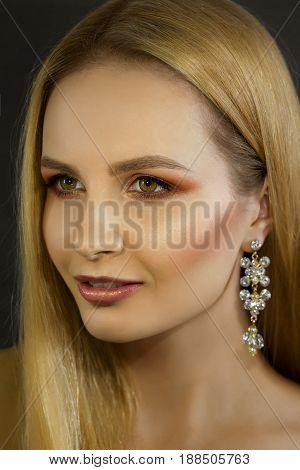 Luxurious portrait of a beautiful woman with shining make-up. Evening make-up with shining skin for blondes lady