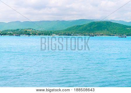 Tropical Green Hilly Island Shore And Blue Calm Clean Sea