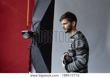 Backstage portrait of hansome Caucasian man working on grey background. Young attractive bearded photographer with camera in his hands is looking forward.