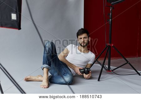 Studio portrait of hansome Caucasian man posing on grey and redwall background. Young attractive bearded photographer with camera in his hands is looking forward.