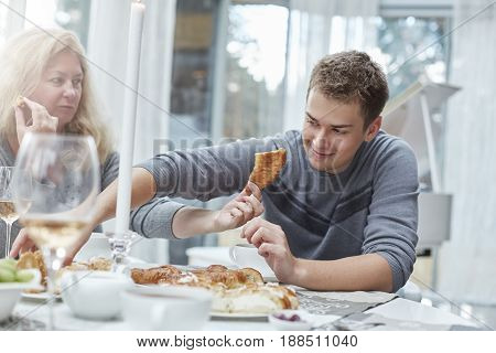 Authentic shot of traditional family sharing experiences of happiness at home and daily life activities. Young hansome male is eating desserts with his mature beautiful mother in a stylish country house. Blond lady is offering fresh bakery for her lovely