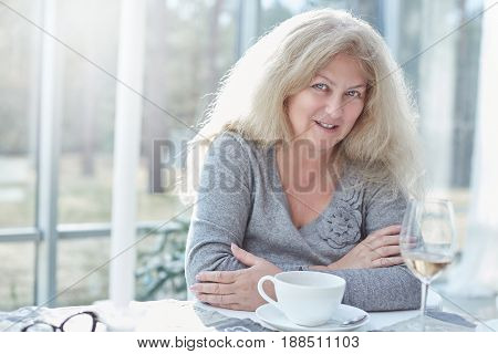 Close up portrait of beautiful blond mature woman looking at the camera cheerfully having lunch in a beautiful light interior of luxury and stylish country house.Daily life activities concept.