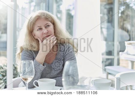 Close up portrait of beautiful blond mature woman looking afar thoughtfully having lunch in a beautiful light interior of luxury and stylish country house.Daily life activities concept.