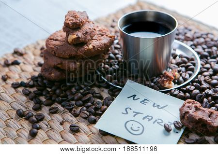 Coffee Cup And Coffee Beans On Wooden Table With Cookies And Notepad With Message On The Sticker