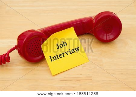 Having a phone in job interview Retro red phone handset with a yellow sticky note and text Job Interview