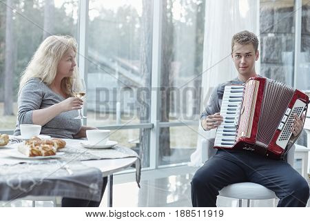 Family moments at home. Young handsome male is looking at the camera and playing accordeon for his senior beutiful mother. Attractive mature Caucasian woman is looking at her adorable son with love drinking white wine during lunch time at stylish luxury h