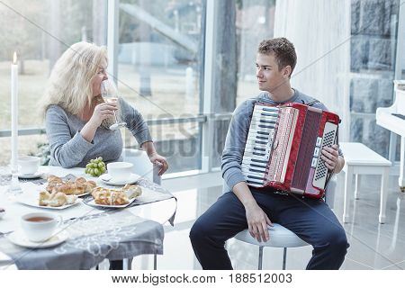 Family moments at home. Young handsome male is playing accordeon for his senior beutiful mother. Attractive mature Caucasian woman is looking at her adorable son with love drinking white wine during lunch time at stylish luxury house.