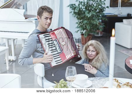Portrait of traditional Caucasian family in a luxury house with stylish interior. Young handsome son is playing accordeon for his mom looking at the camera. Mother is sitting beside him listening with love. Family moments at home.