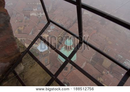 Typical red roofs of Bologna. View from a narrow window with iron grid of Asinelli Tower. Emilia Romagna Italy.