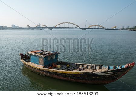Local fishing boat on Han River with Dragon Bridge in background at Da Nang Vietnam.