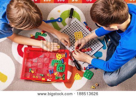 Children playing with toys tool kit. Top view
