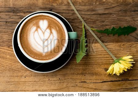 Hot mocha coffee or capuchino with heart pattern and yellow flower and white carnation on the wooden table