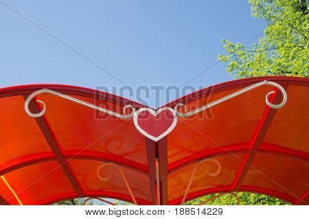 Red roof of a summerhouse with a heart shape on a background of leaves