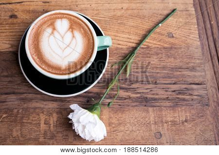 Hot mocha coffee or capuchino with heart pattern and white carnation flower on the wooden table