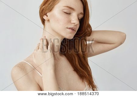 Portrait of tender redhead girl with freckles posing with closed eyes over white background.