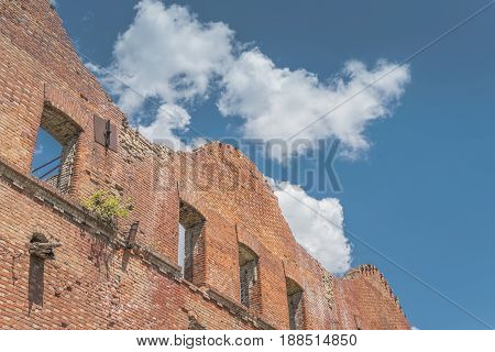 Abandoned house, ruined wall against the blue sky with clouds. Stock image.