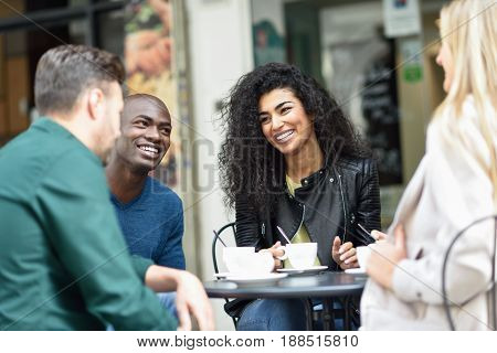 Multiracial group of four friends having a coffee together. Two women and and two men at cafe talking laughing and enjoying their time.