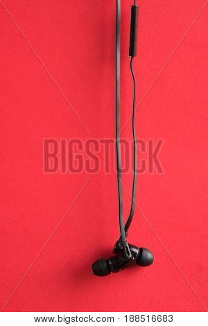 Old back earbuds with red background. In Closeup.