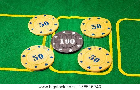 Background of five plastic chips for poker one is different one which in the middle it is more expensive and meaningful than the rest