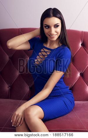 Young sexy girl in sexy blue dress sitting on red sofa. Fashion model with long brunette hair and makeup