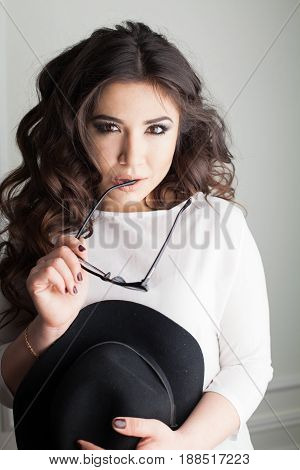 beautiful girl with Hat and glasses in the Studio pozirue curls hairstyle