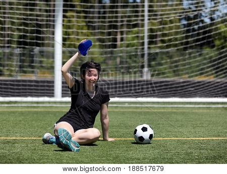Teen age girl pouring cold water on her head to cool down during a hot day on the soccer field