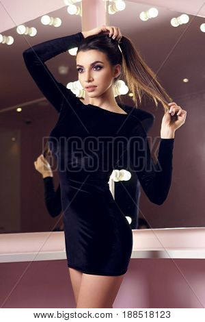 Young sexy girl in short cocktail black dress standing and posing in interior with mirrors and lightning bulbs. Fashion model with long brunette hair and makeup